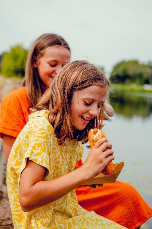Meisjes eten van Coertjens hot dog aan het water
