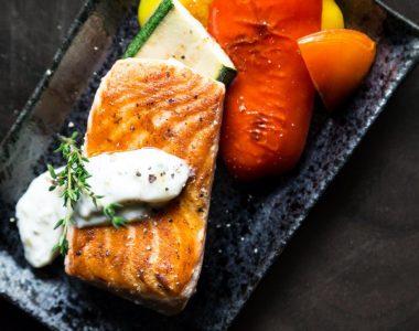 gebakken zalmfilet met tartaarsaus gedresseerd op een zwart bord met groenten